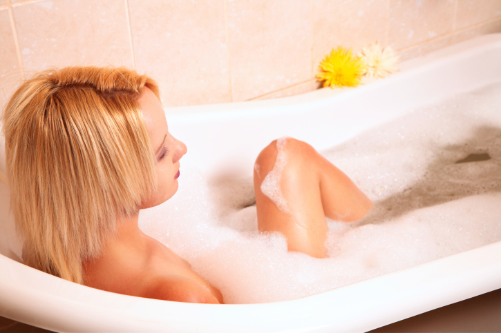 Young blond woman enjoying a foam bath